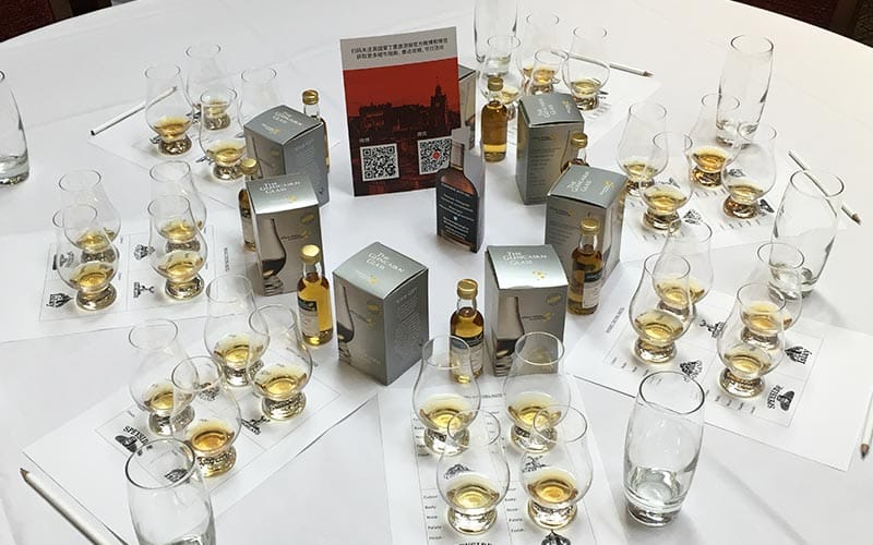 Image of a table with small tester bottles of whiskey and whiskey glasses filled with different types of whiskey