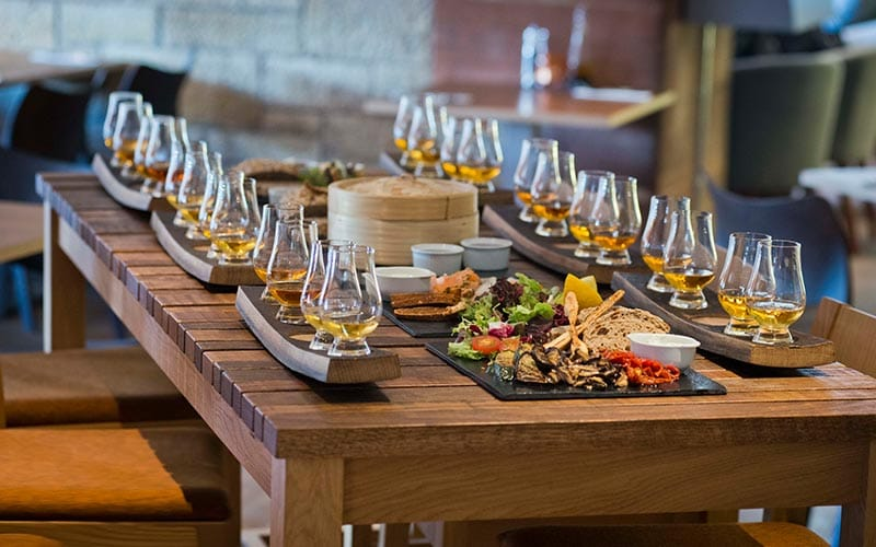 Image of a table with a tray of whiskeys at each seat with some food