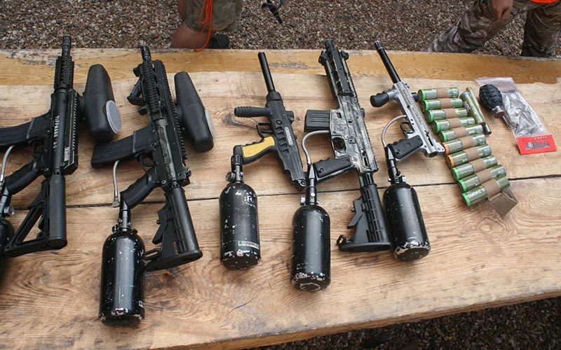 A line of various guns and weapons on a wooden table