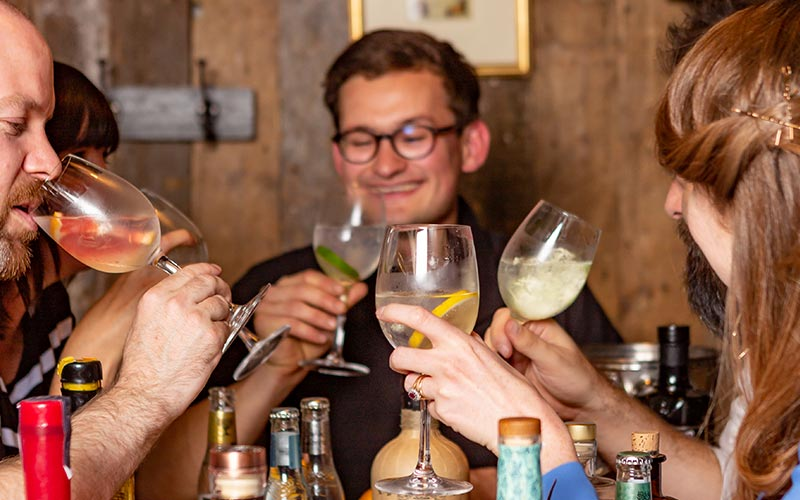 A close up of a group of people drinking gin