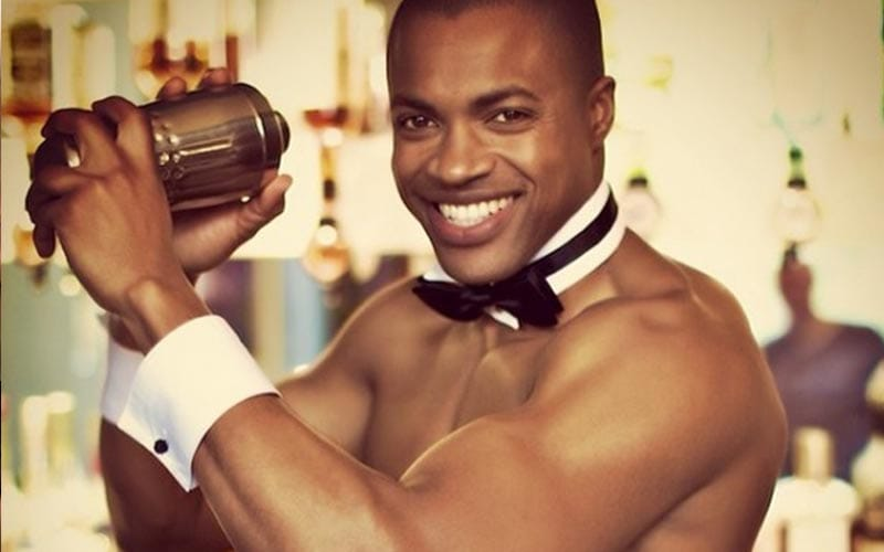 A butler in the buff shaking a cocktail shaker