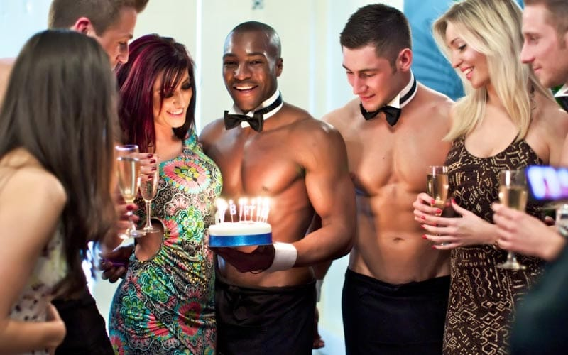 A butler in the buff holding a cake to a woman, whilst others look on