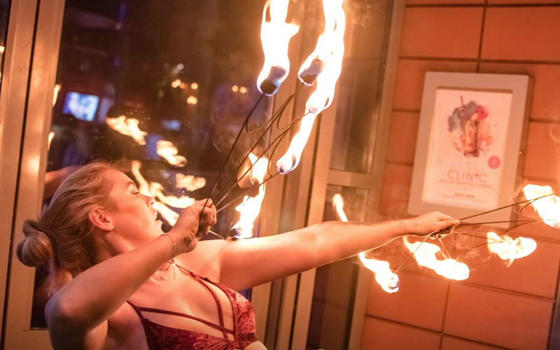 A woman dancing while holding flaming torches