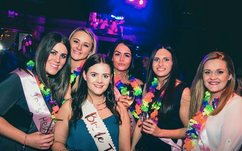 A group of women posing while wearing hen night sashes