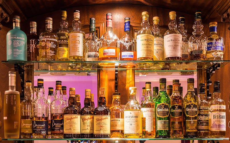 A row of bottles of whisky lined up behind a bar
