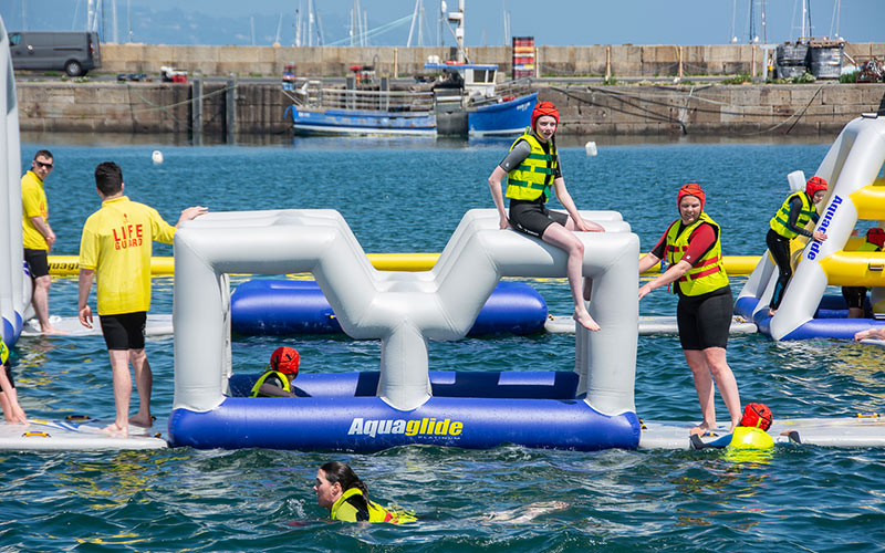 A group of people sitting on inflatables in water