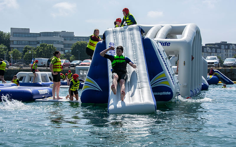 A group of people sliding down inflatable obstacles