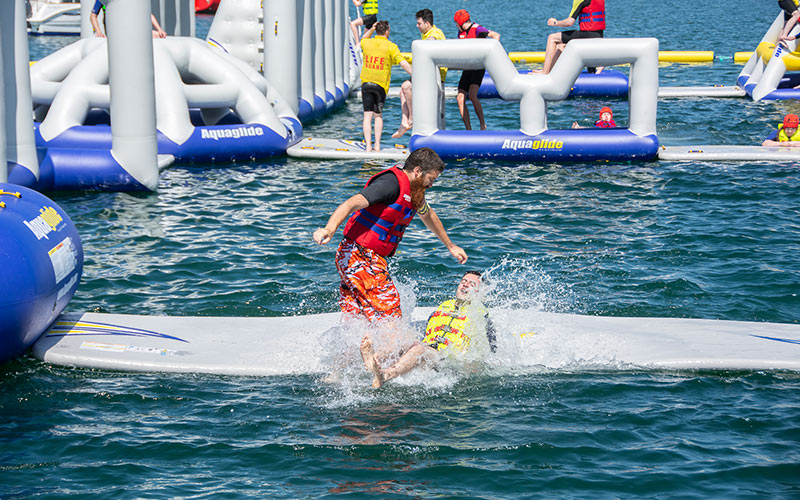 A group of people on inflatable obstacles in the background with two people in the sea in the foreground