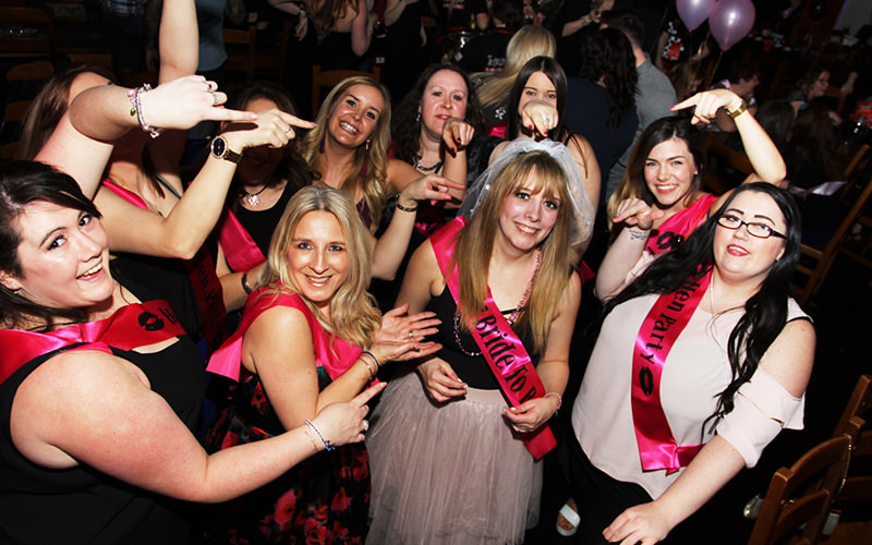 A group of hens wearing sashes point to the bride-to-be who is standing in the middle of the group
