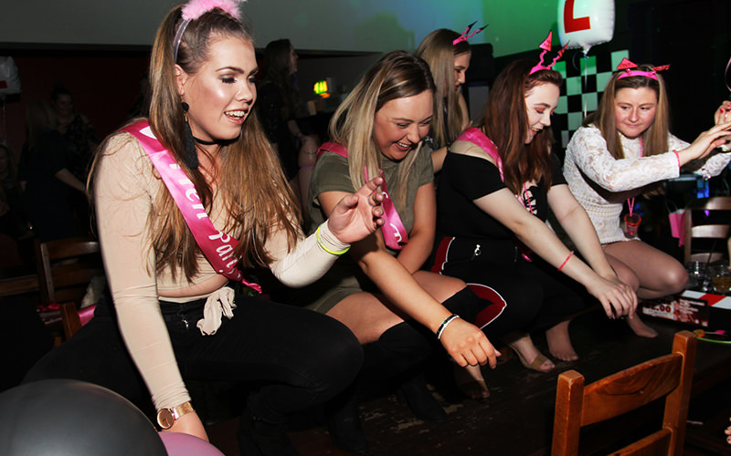 A group of hens wearing sashes while dancing