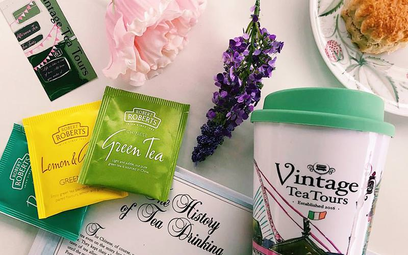 Image of vintage tea tours branded tea bags and hot drinking cup with a lavender branch and pink flower on a table