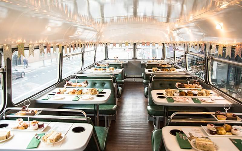 Image of the tables layed out with a two tiered cake and sandwich stand on the top of the double decker bus