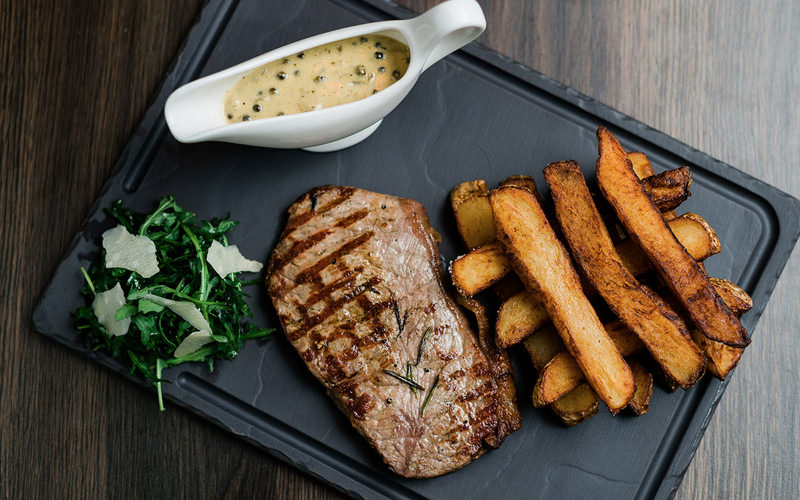 A steak and several chips displayed on a grey tray with a sauce