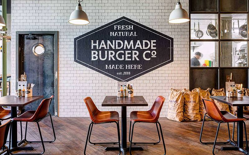 Image of inside handmade burger co with wooden flooring and tiled walls with the logo on the wall with wooden tables and chairs with hanging lighting