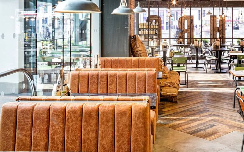 Image of inside handmade burger co with burnt orange booth seating and wooden flooring with lights hanging from the ceiling
