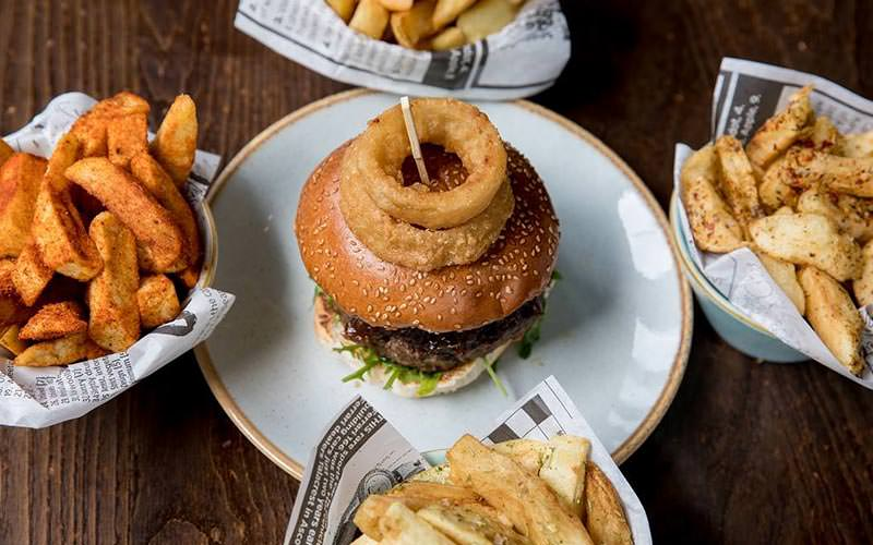 Image of a birdseye view of a burger on a rounded plate with onion rings in the middle of a table with four different type of chips in bowls