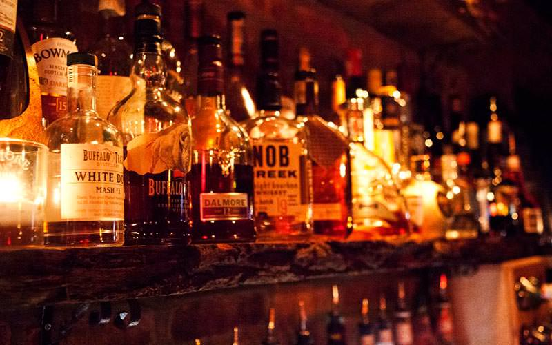 Image of a shelf with a selection of whiskeys lit up