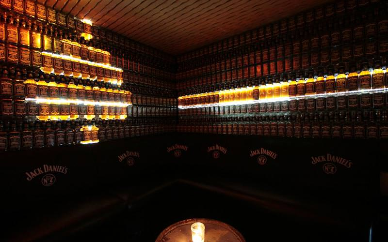 Image of a room filled with jack daniels bottles making the walls and a wooden beer barrel in the middle of the room