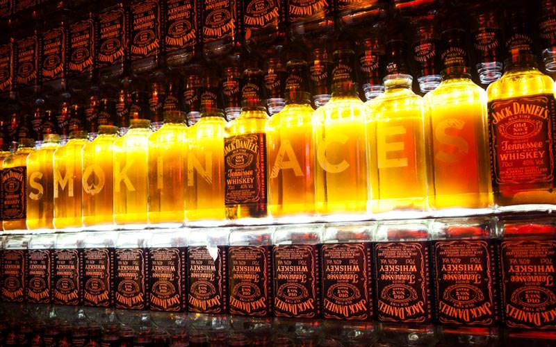 Image of jack daniel bottles with blank whiskey bottles lined up with letters on each spelling out smokin aces and lit up