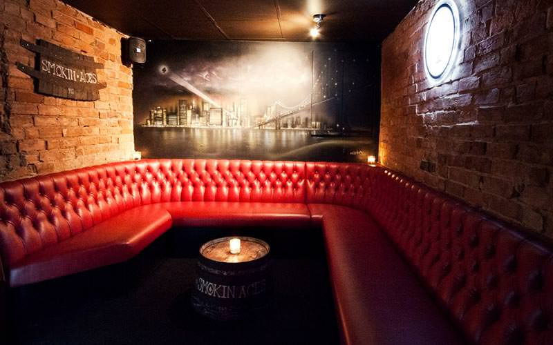 Image of a booth area with a red chesterfield corner seating area with a wooden beer barrel table with a candle on top