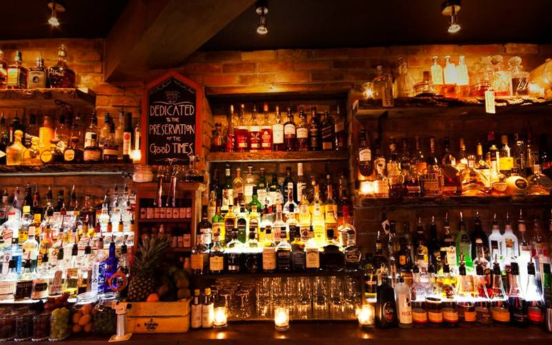 Image of the bar area showing lines of different alcohol with spotlights shining on them