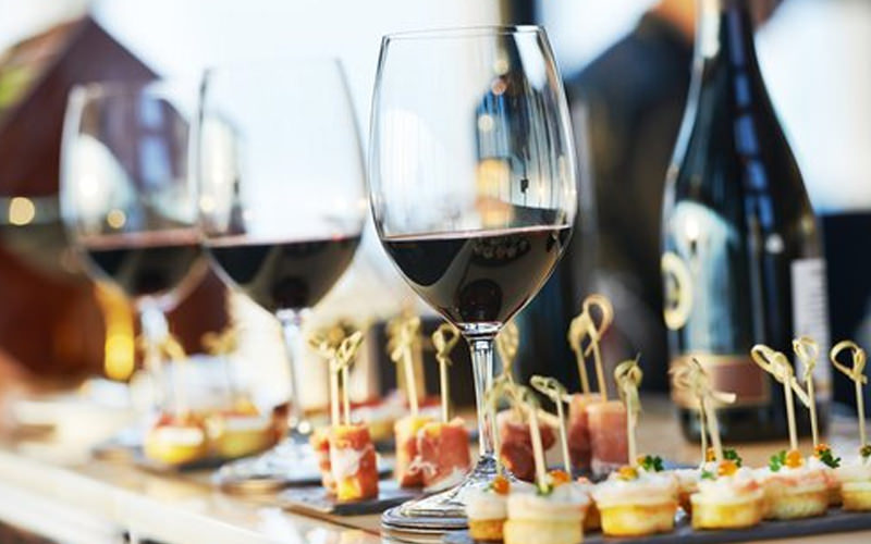 Three glasses of wine and a selection of food of a table