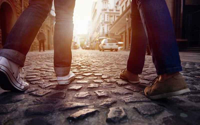 A close up of two people walking on a cobbled street
