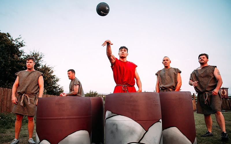 A man attempting to throw a ball into a barrel while four men watch