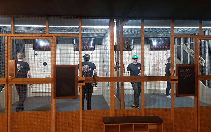 A group of people throwing axes at targets