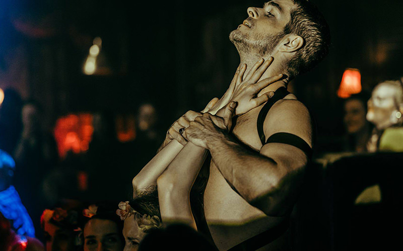 A topless man holding a woman's hands to his body