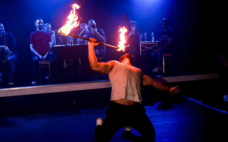 A man breathing fire on stage
