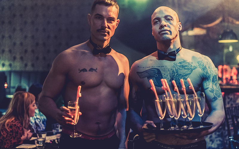Two topless waiters holding glasses of champagne with willy straws in them