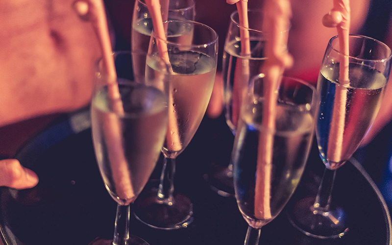 A close up of several glasses of champagne with willy straws in them