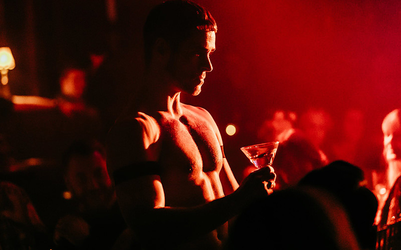 A topless man holding a glass of champagne