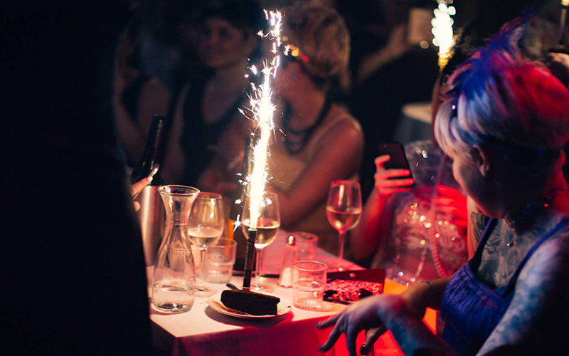 A group of women sitting at a table with glasses of wine and a sparkler