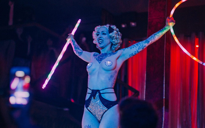 A half-naked woman performing a burlesque routine
