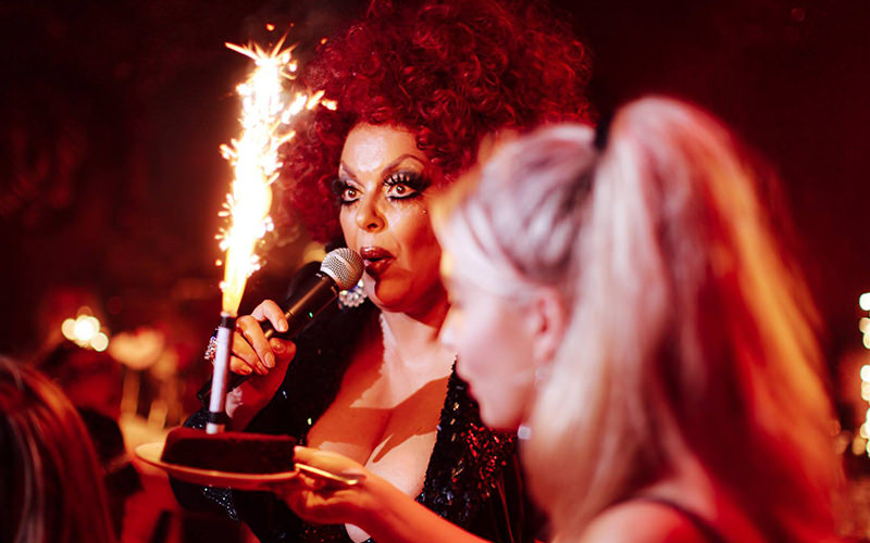 A drag queen singing in a club