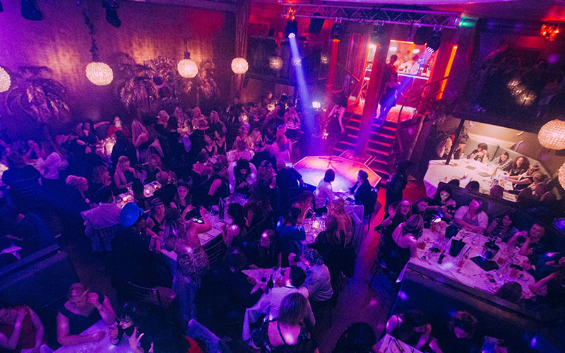 A view of a busy cabaret club with several tables
