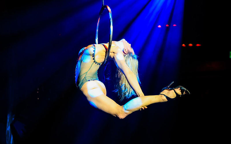 A woman suspended in the air from a hoop