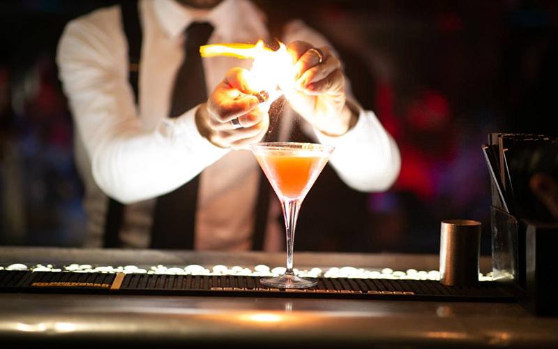 A man making a cocktail at a bar