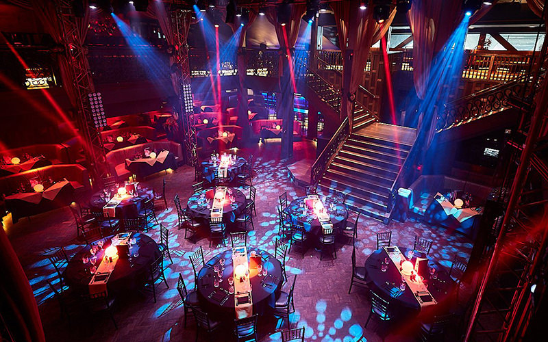 A view of a cabaret club with several round tables