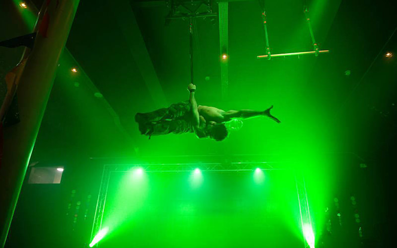 A man performing on a stage suspended from a rope