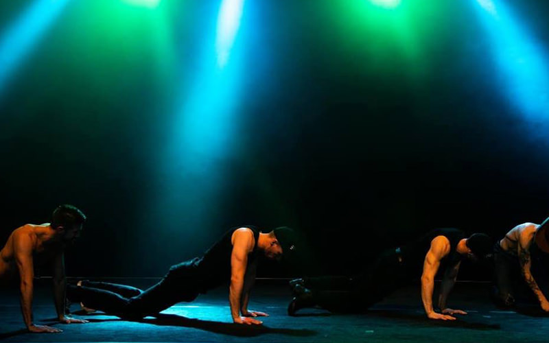 A group of men performing push-ups on a stage