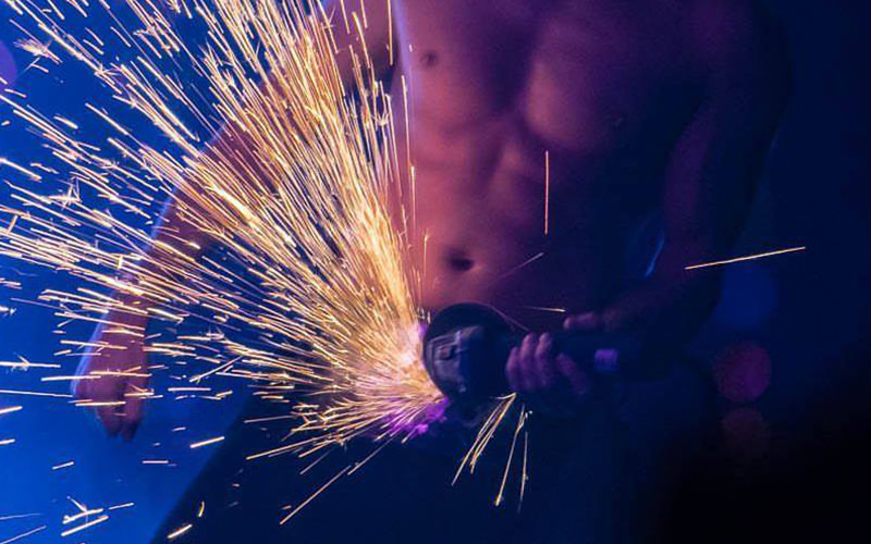 A man holding an axel grinder to his crotch, creating sparks