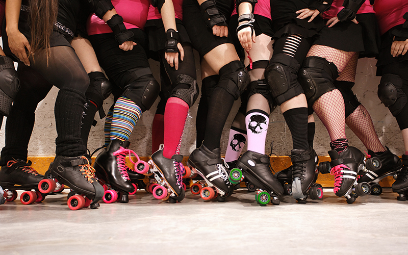 A close up of a group of girls wearing roller skates