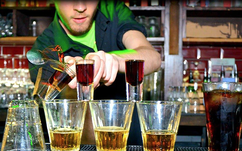 A man pouring alcohol into large glasses