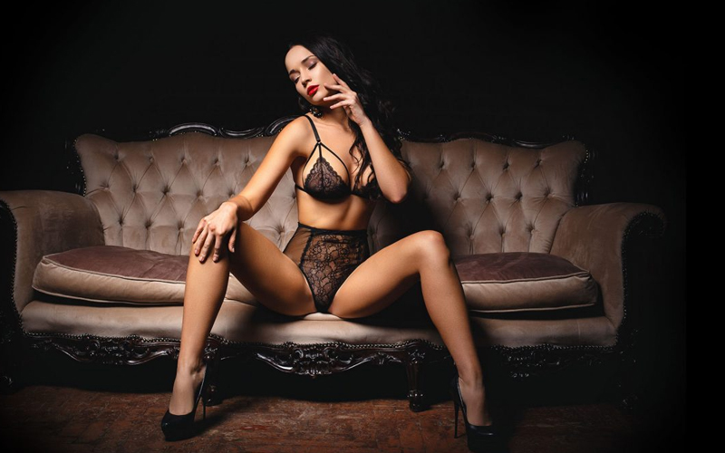 A woman in black lingerie sitting on a settee