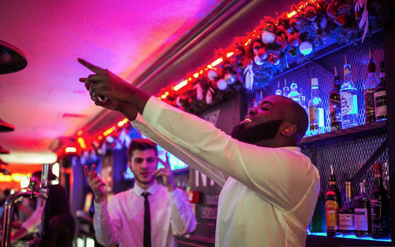 A bartender dancing while serving drinks
