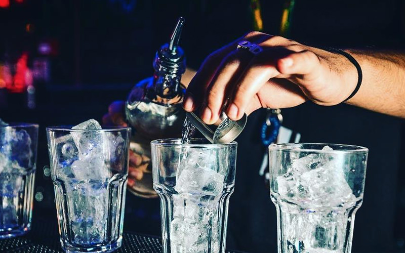 A pair of hands adding a cocktail mixture into several glasses
