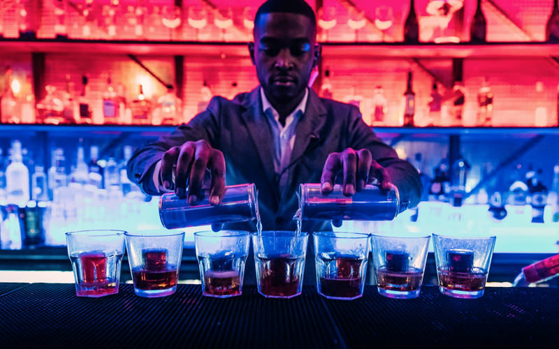 A man making several cocktails at once